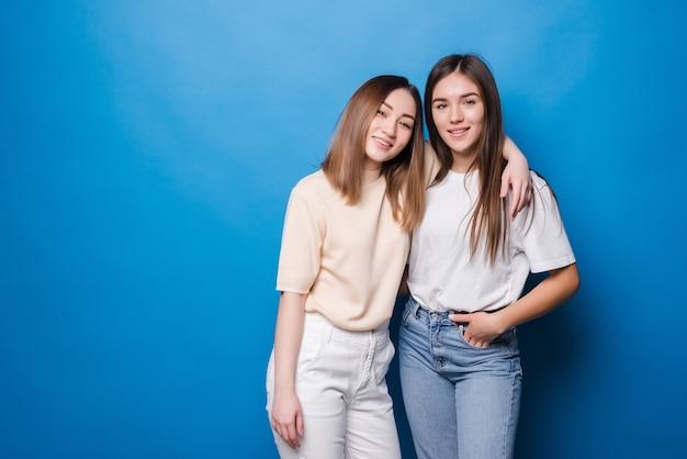Voor altijd vrienden. twee leuke mooie meisjesvrienden die met glimlach op blauwe muur stellen