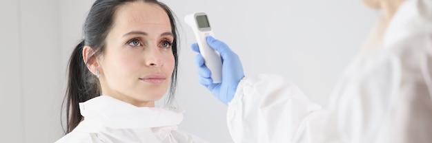 Voor arts in beschermend pak wordt de lichaamstemperatuur gemeten met een thermometer na het werk