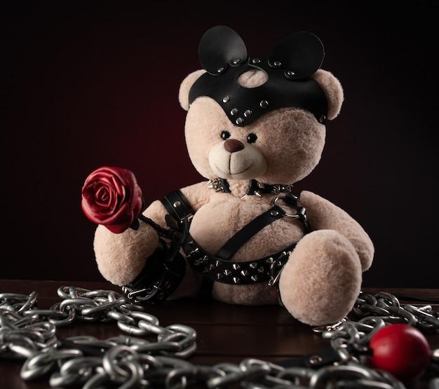 Voor bdsm is een speelgoedteddybeer gekleed in leren riemen en een masker een accessoire