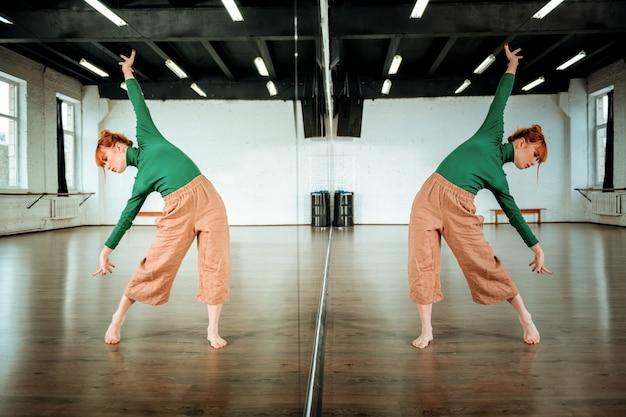 Voor dansles. leuke roodharige dansleraar die een groene coltrui draagt die neigingen doet