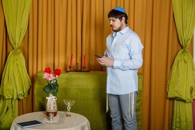 Vóór de choepa-ceremonie spreekt de bruidegom in de synagoge, terwijl hij op de bruid wacht, door een sms te typen aan de telefoon. horizontale foto
