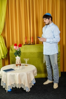 Vóór de choepa-ceremonie spreekt de bruidegom in de synagoge, terwijl hij op de bruid wacht, door een sms te typen aan de telefoon. verticale foto