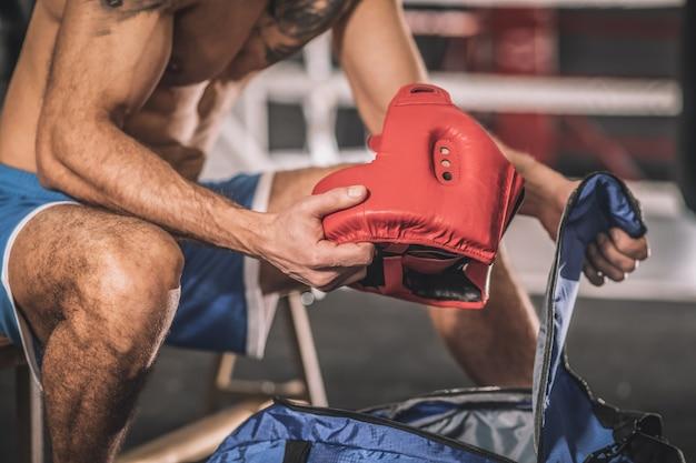 Voor de training. gespierde man zit in een kleedkamer in een sportschool