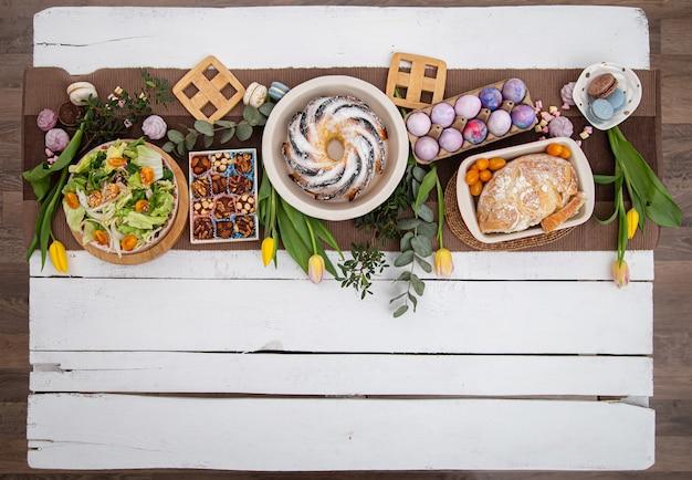 Voor een feestelijke paastafel geserveerd met eten. het concept van de paasvakantie. plat lag