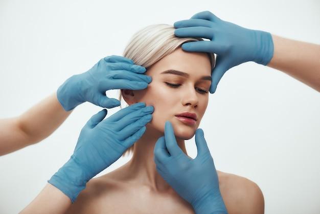 Voor gezichtschirurgie mooie blonde vrouw die ogen gesloten houdt terwijl artsen in blauwe medische