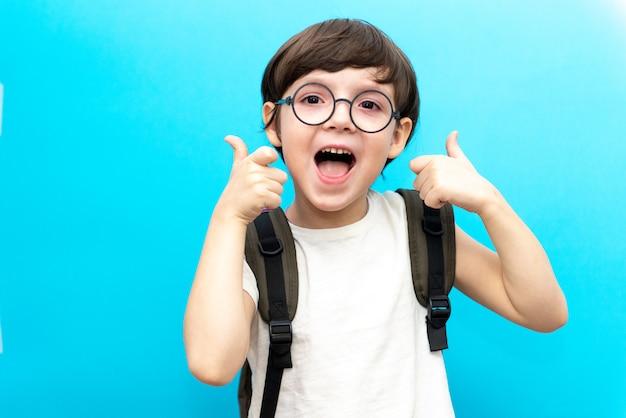 Voor het eerst naar school. gelukkige glimlachende jongen met omhoog duim. een kind van de basisschool in uniform. peuter binnenshuis op een blauwe muur.