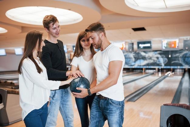 Voor het geluk. jonge, vrolijke vrienden vermaken zich in het weekend in de bowlingclub