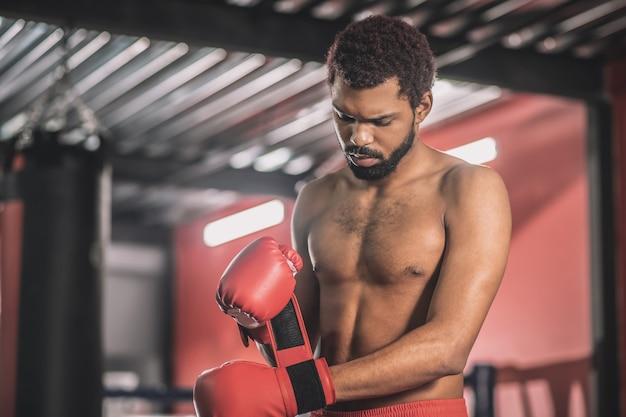 Voor het gevecht. atleet met donkere huid typt zijn handen met een rood verband