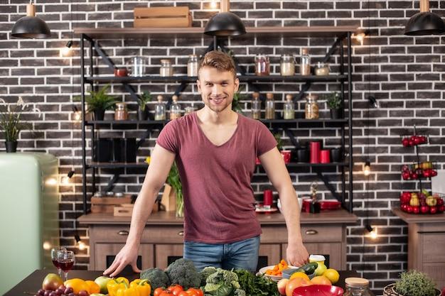 Voor het koken. liefhebbende knappe man voelt zich opgewonden en opgewekt terwijl hij voor het avondeten kookt voor een lieve vrouw