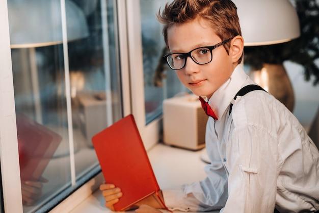 Voor het raam staat een jongen in een overhemd met een rode vlinderdas en een bril, met een rood boek in zijn handen.