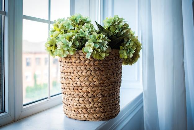 Voor het raam staat een rieten mand met lichtgroene hortensia's