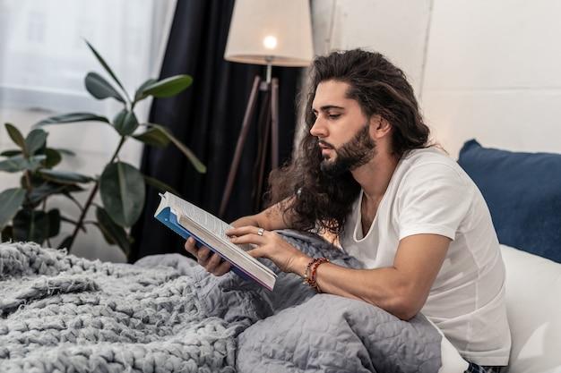 Voor het slapen. aardige knappe man die zijn favoriete boek leest voordat hij in slaap valt