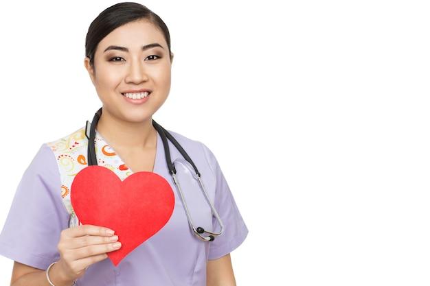 Voor je zorgen. een aziatische vrouwelijke arts die rood papier hart lacht warm geïsoleerd op wit