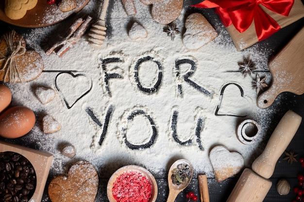 Voor jou geschreven op meel. hartvormige peperkoekkoekjes, kruiden, koffiebonen en bakbenodigdheden