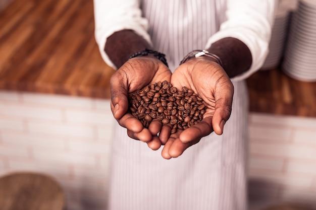 Voor koffie. bovenaanzicht van heerlijke gebrande koffiebonen die in handen zijn
