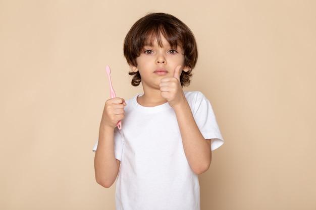 Voor portret, kind jongen met tandenborstel in zijn handen in wit t-shirt op roze bureau