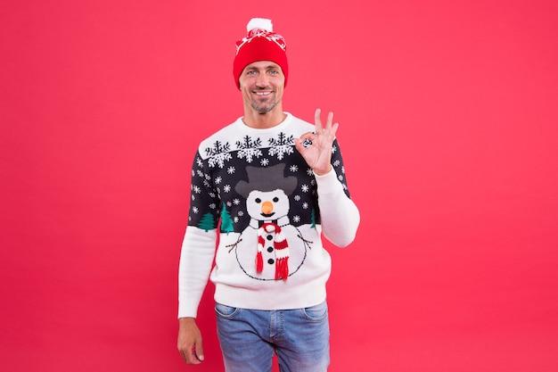 Voor seizoenscomfort. gelukkig man geeft ok teken in mode sneeuwpop jumper. koud weer mannelijke stijl en mode. modetrends voor de winter heren. blijf warm met een opvallend modeontwerp.