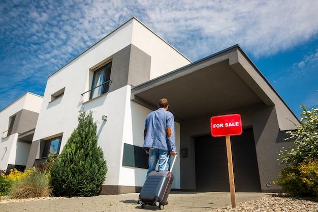 Voor verkoop onroerend goed concept, man die het huis verlaat vanwege de economische crisis