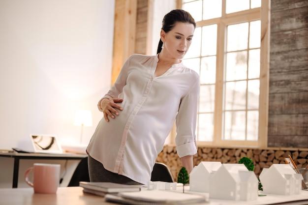 Voor zwangerschapsverlof. ambitieuze mooie zwangere ontwerper model kijken terwijl buik aanraken en leunend op tafel