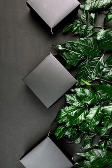 Voor zwarte geschenkdoos een donkere tafel met groene bladeren aan de zijkanten, creatieve lay-out, plat leggen, natuurconcept