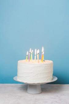 Vooraanzicht aangestoken kaarsen op verjaardagstaart
