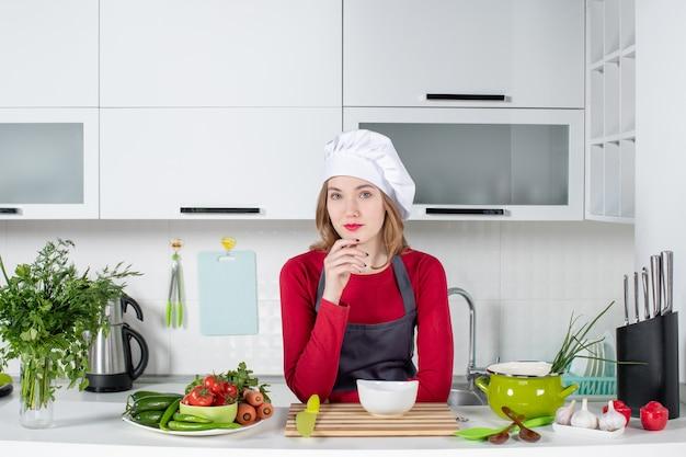 Vooraanzicht aardige vrouwelijke chef-kok in uniform die achter de keukentafel staat
