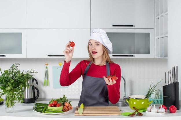 Vooraanzicht aardige vrouwelijke kok in schort die tomaten omhoog houdt