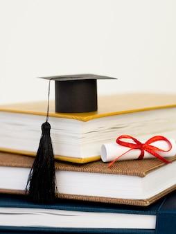 Vooraanzicht academische cap op stapel boeken