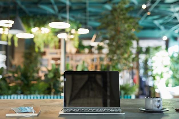 Vooraanzicht achtergrondafbeelding van geopende laptop met leeg scherm in modern milieuvriendelijk café-interieur versierd met verse groene planten, kopieer ruimte