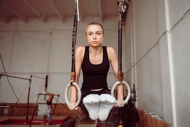 Vooraanzicht atletische vrouw training op gymnastiekringen