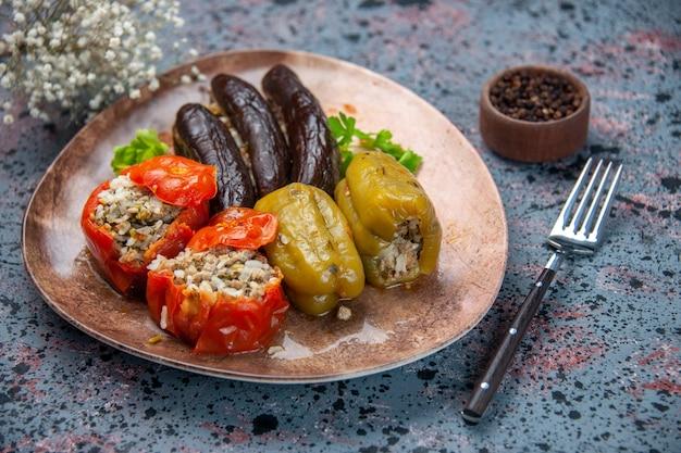 Vooraanzicht aubergine dolma met gekookte tomaten en paprika gevuld met gehakt binnen plaat op blauwe achtergrond voedsel schotel kleur diner maaltijd