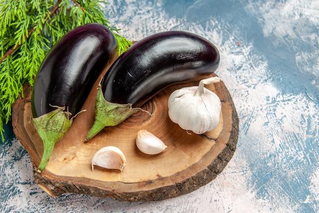 Vooraanzicht aubergines knoflook op boom houten bord op blauw-witte achtergrond