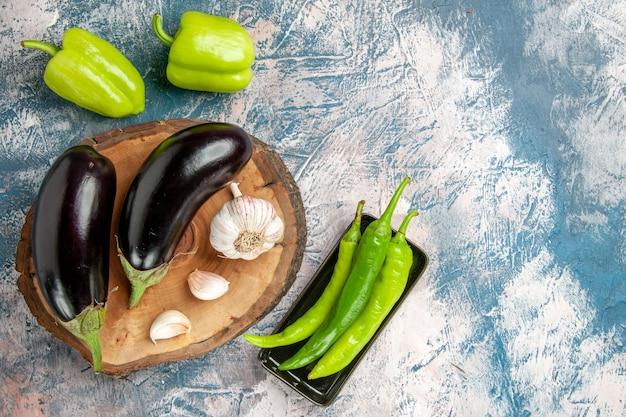 Vooraanzicht aubergines knoflook op boom houten bord paprika's hete groene paprika's op zwarte plaat op blauw-witte achtergrond vrije ruimte