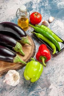 Vooraanzicht aubergines op boom houten bord hete pepers op zwarte plaat knoflook groene en rode paprika's tomaat fles olie op blauw-witte achtergrond