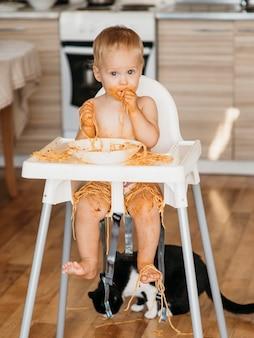 Vooraanzicht babyjongen die een puinhoop met pasta maakt