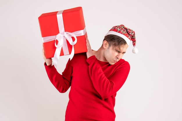 Vooraanzicht bang jonge man met kerstmuts staande op wit