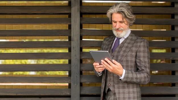 Vooraanzicht bebaarde elegante man met tablet Premium Foto