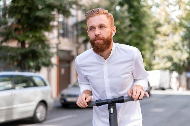 Vooraanzicht bebaarde moderne man op scooter buiten