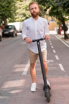 Vooraanzicht bebaarde moderne man op scooter