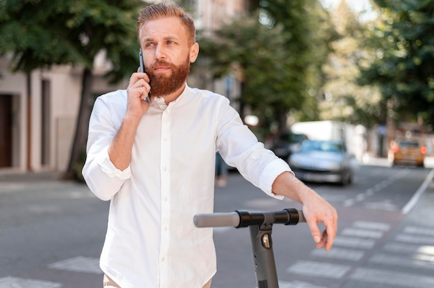Vooraanzicht bebaarde moderne man praten aan de telefoon op scooter