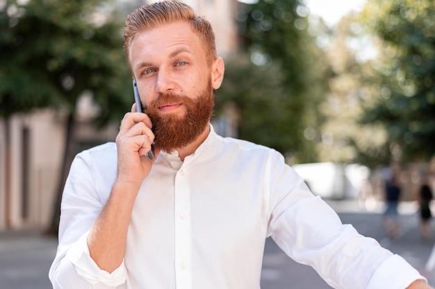 Vooraanzicht bebaarde moderne man praten aan de telefoon