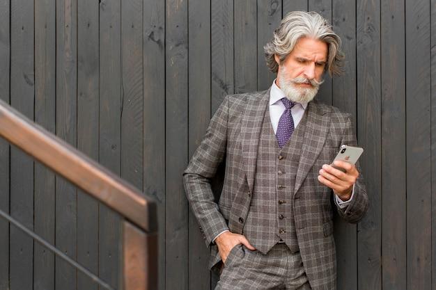 Vooraanzicht bebaarde volwassen man mobiele telefoon browsen Premium Foto