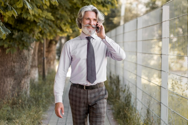 Vooraanzicht bebaarde volwassen man praten aan de telefoon