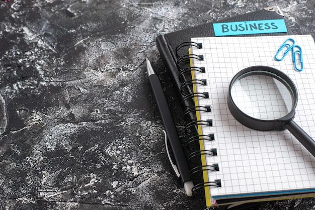 Vooraanzicht bedrijfsnota met blocnotes en vergrootglas op donkere achtergrond
