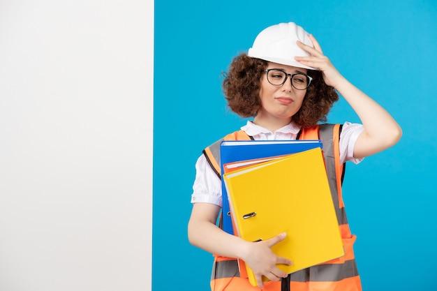 Vooraanzicht benadrukt vrouwelijke bouwer in uniform op blauw