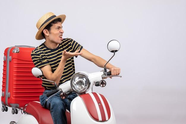 Vooraanzicht benieuwd jonge man met strooien hoed op bromfiets