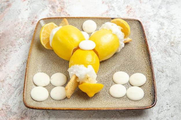 Vooraanzicht bevroren citroenen met witte snoepjes op lichte witte tafel fruitdrank cocktailsap