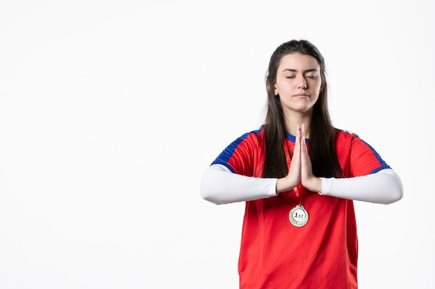 Vooraanzicht biddende vrouwelijke speler met medaille
