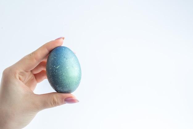 Vooraanzicht blauw ontworpen ei in vrouwelijke hand op witte achtergrond lente kleurrijke novruz vakantie concept sierlijke Premium Foto