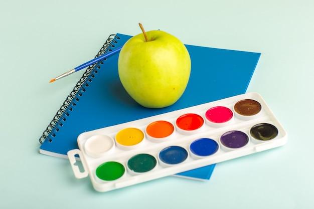 Vooraanzicht blauw voorbeeldenboek met verse groene appel en verf op ijsblauw oppervlak